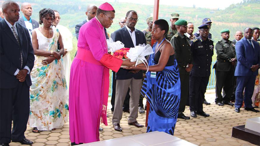 Bishop Anaclet Mwumvaneza receives a wreath to lay on the tomb of Nyange Secondary School students in Ngororero District yesterday. The students, who are all national heroes recogn....