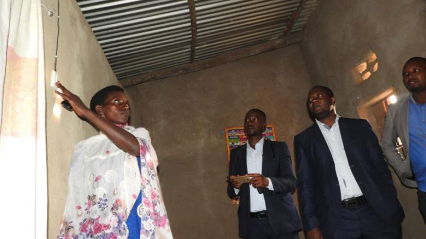 Murekatete tests her newly-acquired solar system as EDCL chief Emmanuel Kamanzi and Ignite official watch. / Kelly Rwamapera