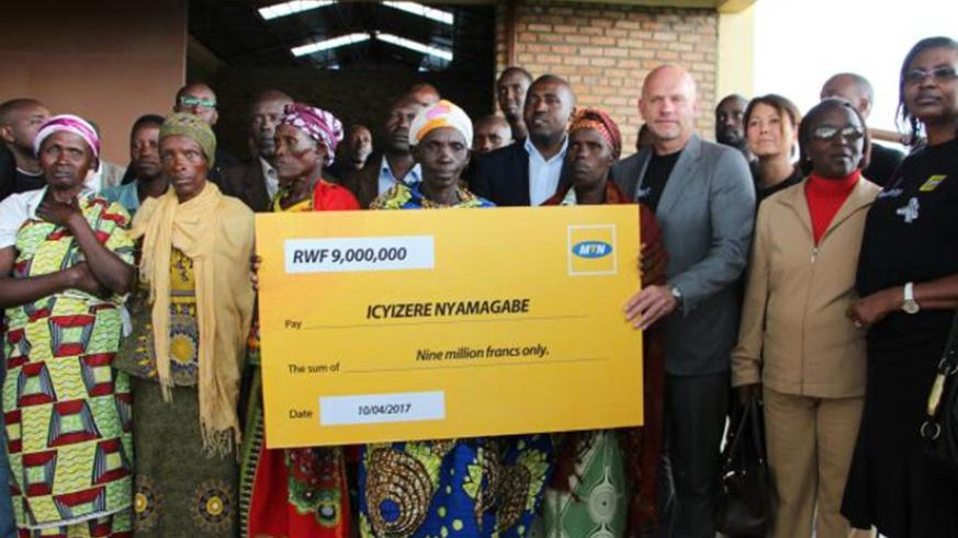 MTN CEO Bart Hofker (3rd right) hands over a dummy cheque for the donation on Monday. The money will benefit survivors in Maryohe village.  (Photos by Eddie Nsabimana)