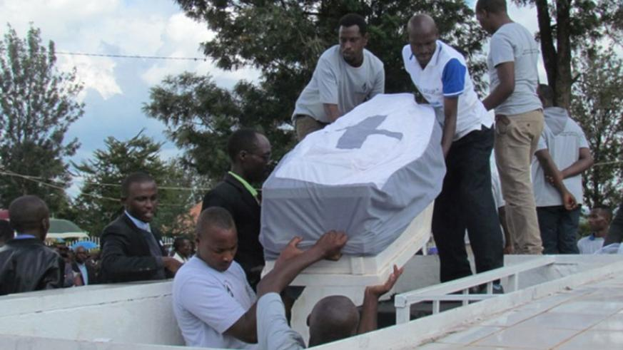 Remains of some of the 1994 Genocide against the Tutsi victims being lowered into a grave at Kiziguro memorial. (Photos by K. Rwamapera)