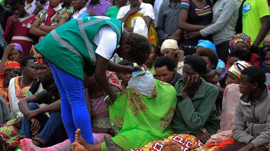 A volunteer attends to a trauma victim at yesterday's commemoration event at Murambi Genocide Memorial, home to some 50,000 victims of the 1994 Genocide against the Tutsi. (All pho....