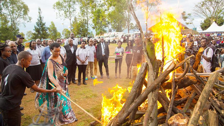 Speaker of Parliament Donatille Mukabalisa lights a fire for a night vigil at Nyanza Genocide memorial in Kicukiro District, the final resting place for some 11,000 victims of the ....