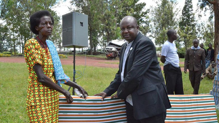 Mutagoma hands over a mattress to one of the Genocide survivors who were given mattresses in Kirehe. / Kelly Rwamapera