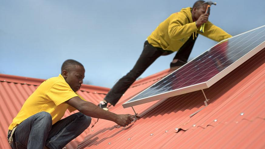 Technicians install a solar system. Government targets 22% off-grid connections by end of next year. / File