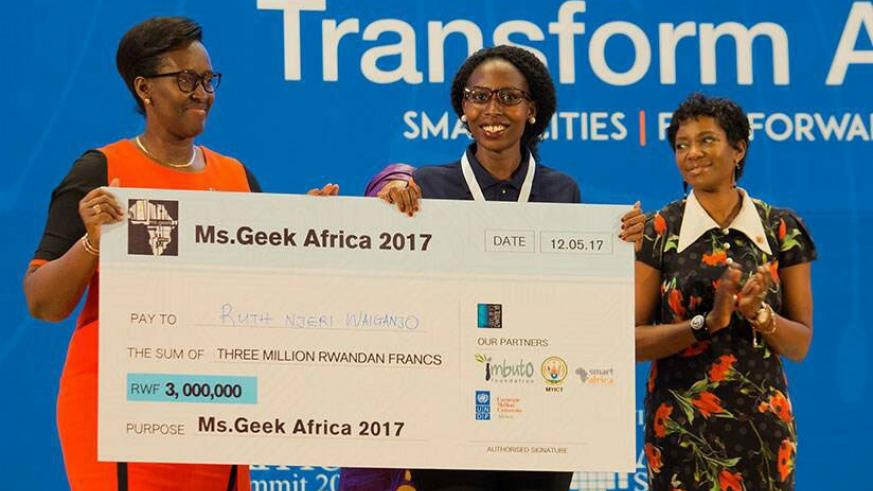 First Lady Jeannette Kagame hands Ms Geek Africa winner Waiganjo her prize.