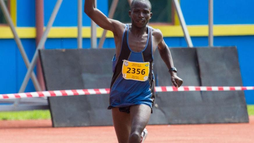 Jean Baptiste Ruvubi waves to the cheering crowd as he crosses the finish line at the 2015 Kigali Peace Marathon to finish second in the men's full marathon. (File)