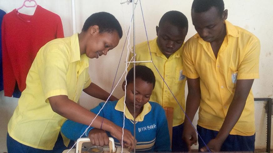 Kelly Umwiza (left) shows her peers how to use a sewing machine. (Photos by Remy Niyingize)