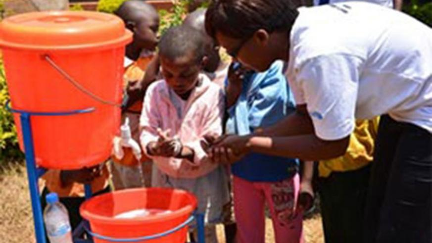 An elder helping and teaching children how to wash hands with soap at the ECD centre. (Courtesy photos)