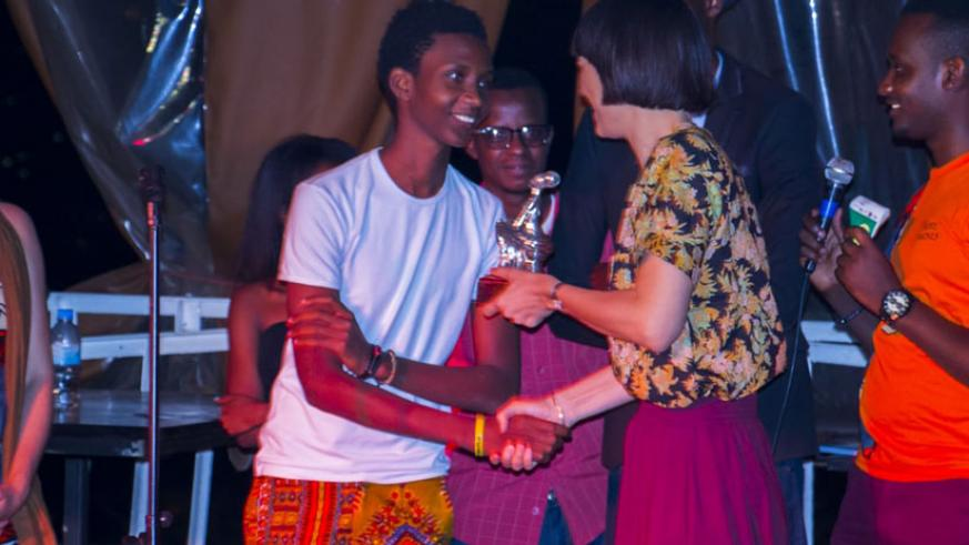 Kivumbi King receives a prize for emerging the winner at Kigali Vibrates with Poetry. Photo: Igihe.com