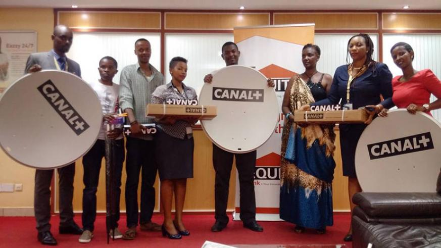 Equity Bank's Niragira (second right) poses for a photo with some of the clients and their prizes. / Joan Mbabazi