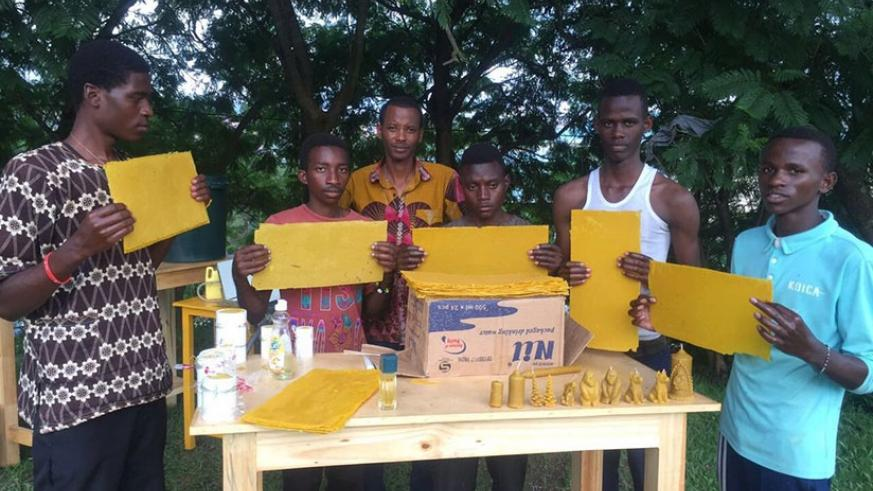 Kanimba (middle) and some of the trainees demonstrate how to make candles from bee wax. The enterprising youth also makes honey (below) among other products. / Photos: Frederic Byumvuhore.