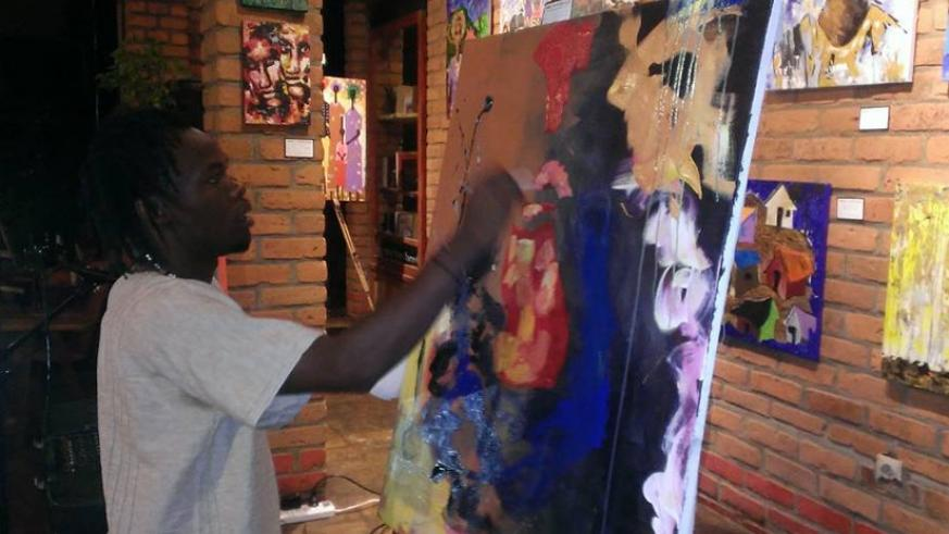 Artist Willy Karekezi demonstrates how live painting is done during the opening of his exhibition at the Heaven Restaurant on Saturday.  Moses Opobo.