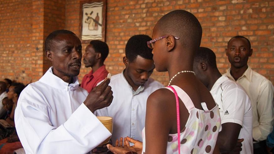 A cleric serves Holy Communion to a Christian at St Michel Cathedral during Assumption Day mass in Kigali yesterday. N. Imbabazi