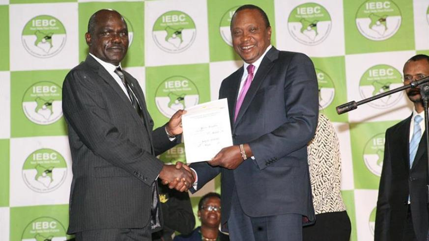 President Uhuru (R) receives the certificate as the winner of presidential elections from Independent Electoral and Boundaries Commission (IEBC) Chairman Wafula Chebukati (L, Front....