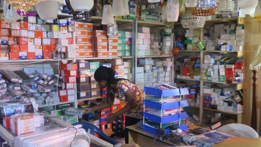 A businesswoman arranges commodities in her hardware shop in Kigali .  File