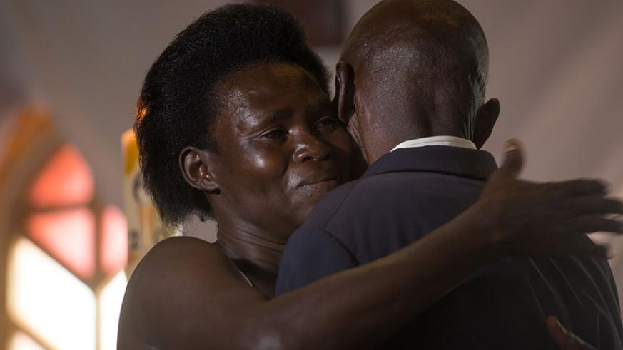 A Genocide survivor, Anne-Marie Uwimana, hugs Celestin Habinshuti, a former Genocide convict who brutally killed two of her children during the 1994 Genocide against the Tutsi. Thi....