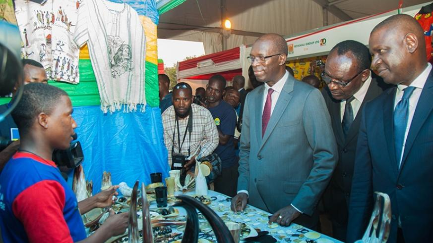 Prime Minister Anastase Murekezi (C), Trade and Industry minister Francois Kanimba (2nd R) and Private Sector Federation chairperson Benjamin Gasamagera visit one of the stands dur....