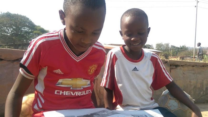 Pupils reading a newspaper after school. Reading stories equips you with several important life skills. / Dennis Agaba