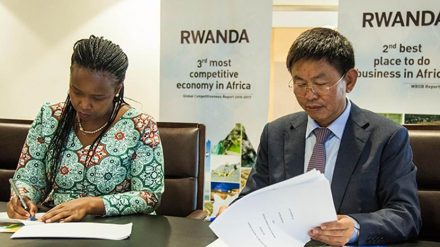 Akamanzi (L) and Zhang sign the MoU to setup a manufacturing plant. Nadege Imbabazi.