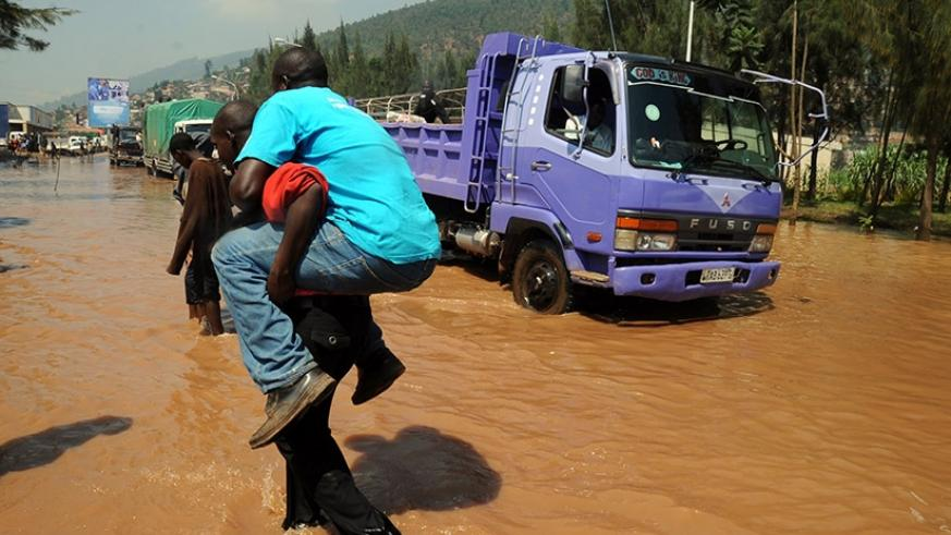 A man is carried across a flooded Nyabugogo highway in the past. File.