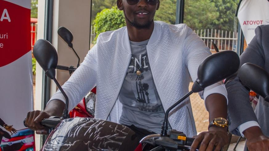 Meddie unveils some of the motorbikes to be won in the Tunga promotion. Net photos