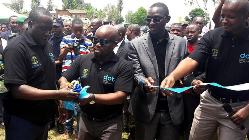 The Minister for ICT, Jean-Philibert Nsengimana (C), and Jean-Marie Vianney Gatabazi (L), the governor of Northern Province, cut a ribbon to launch the Tumba Smart Village Initiati....