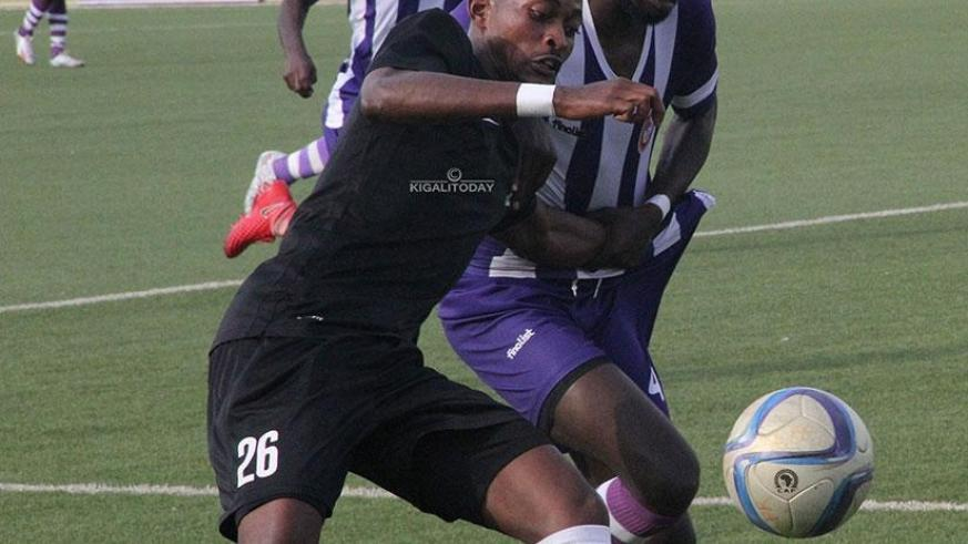 APR FC forward Issa Bigirimana is challenged by a Sunrise defender during Saturday's league opener at Kigali Stadium. Courtesy