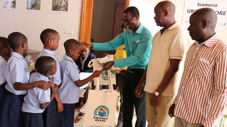 Karongi Environment Museum manager André Ndabaga, flanked by Edition Bakame officials, rewards children after a reading competition at the museum. (M. Nkurunziza)