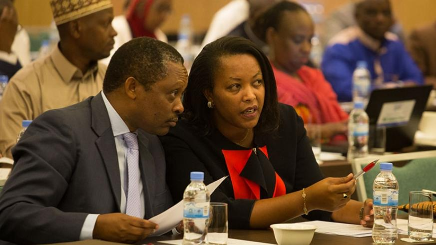 Prof. Anastase Shyaka, the chief executive of Rwanda Governance Board (L), chats with Gender and Family Promotion minister Esperance Nyirasafari during yesterday's  meeting. (All p....