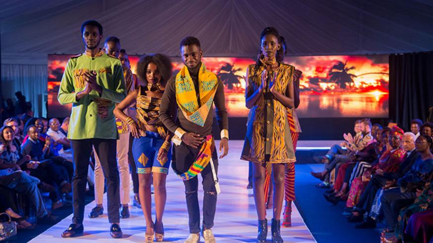 Fashion designer David Gulu (centre) from Dr Congo with his models at the Kigali Fashion Week 2017.