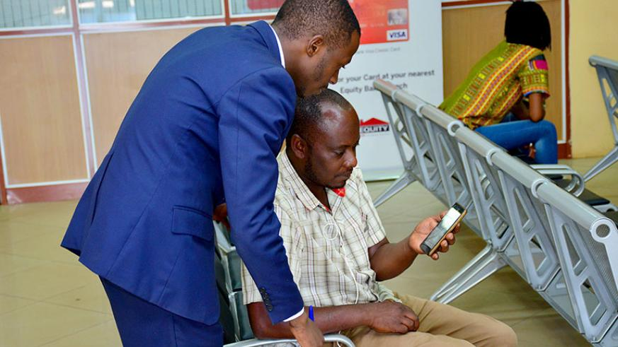 Bank staff helps a customer to set up a mobile banking service on his phone. / Lydia Atieno