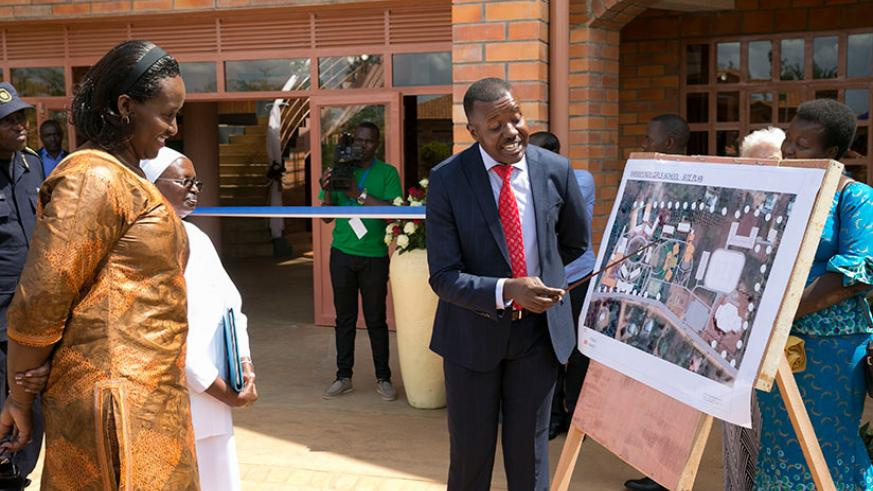 First Lady Jeannette Kagame observing the blueprint of Maranyundo Girls School's new educational facilities during the the first A Level graduation ceremony at the school yesterday....
