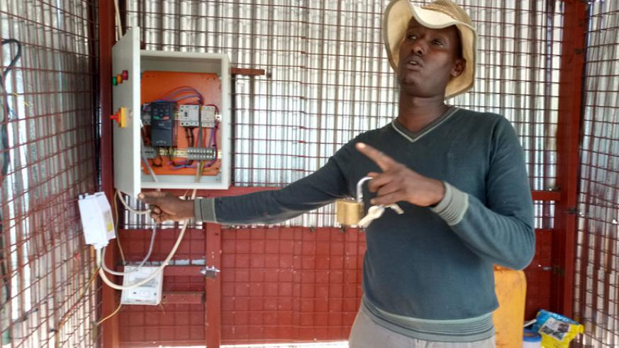 Gatete explains how the solar-powered irrigation system works, in Nyagatare District, on Thursday. / Emmanuel Ntirenganya