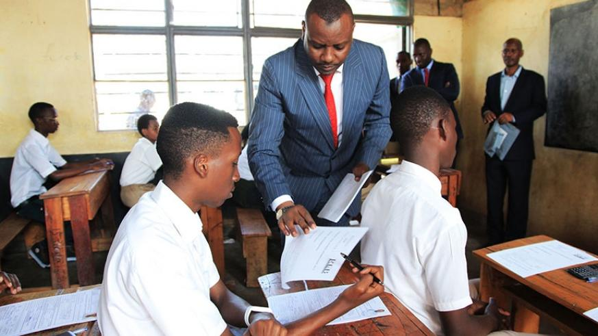 The State Minister for Primary and Secondary Education, Isaac Munyakazi, distributes examination scrips to the candidates at GS Remera as national O and A-Level examinations starte....
