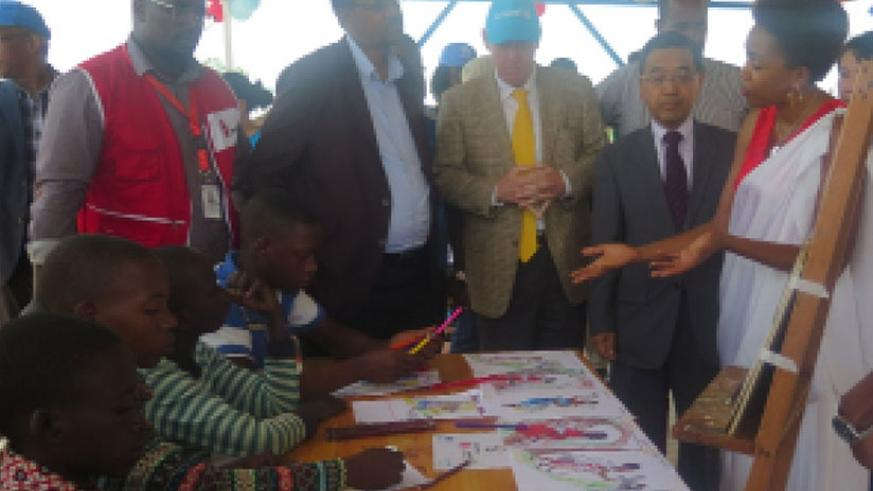 Ambassador Takayuki (2nd Right) and other officials inspect children  painting art work at Mahama Refugee Camp during their visit last week.   / Eddie Nsabimana.