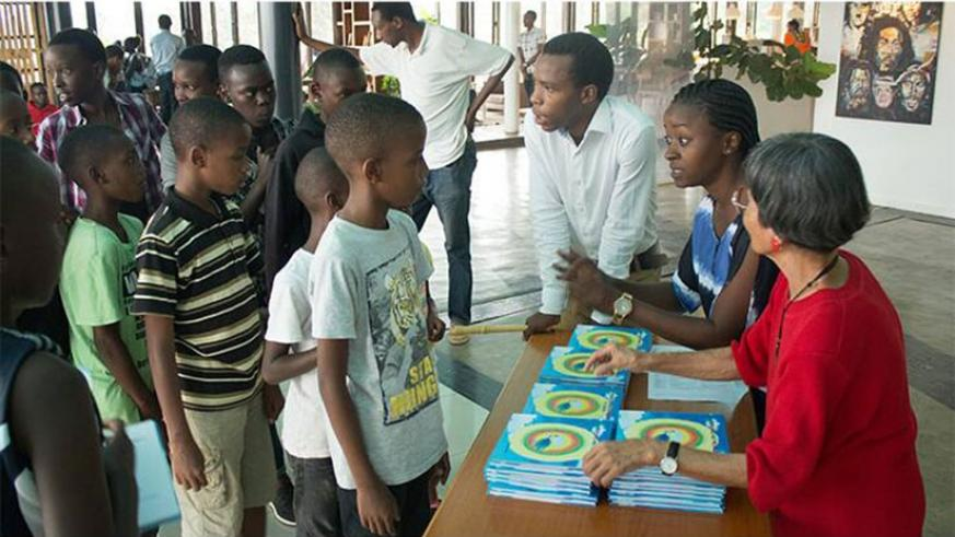 Children participating in the programme receive study material. / By Diane Mushimiyimana.