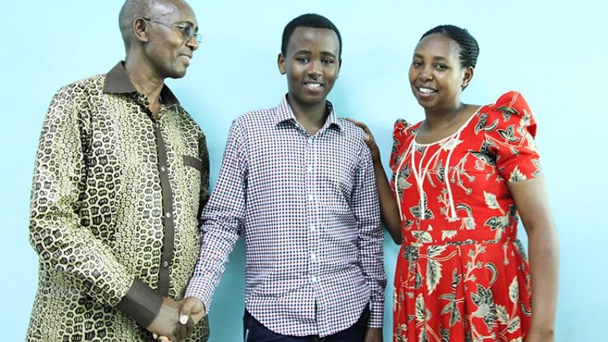 PLE star Sam Musoni Nshuti's parents, Edson Musoni and Aloysie Mutoni, pose for a photo with their son at The New Times Publications headquarters in Kigali yesterday. (Sam Ngendahimana)