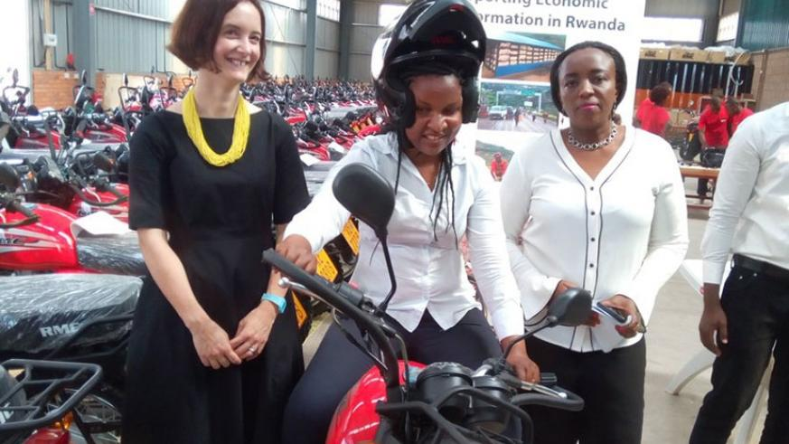 One of the land officers tries out a motorcycle as Mukamana (right) and DFID's Metcalf (left) look on during the handover ceremony at Bollore Warehouse at the Special Ezonomi....