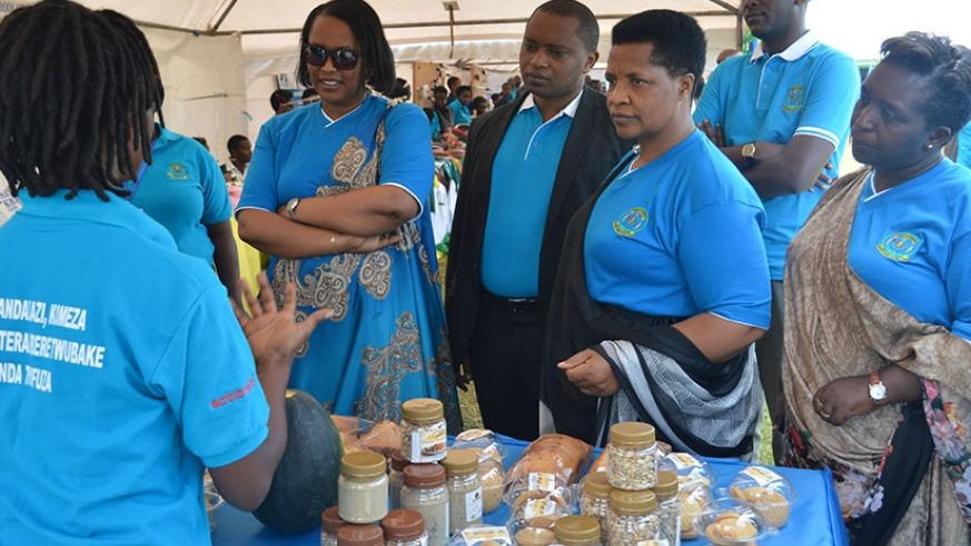 A female exhibitor explains to officials how she makes products from pumpkin seeds during national celebrations of the International Women's Day in Shyogwe Sector, Muhanga Di....