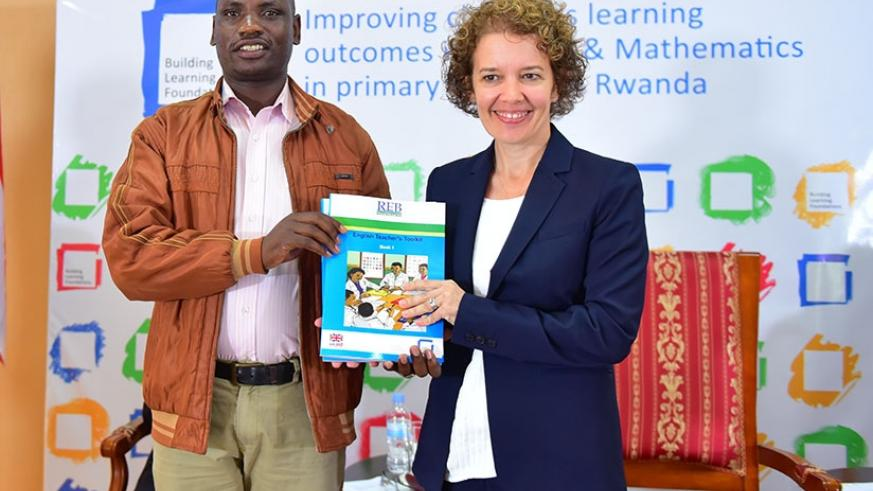 Amb. Lomas (right) gives a teachers' toolkit book to a teacher under the Building Learning Foundations programme. (Kelly Rwamapera)