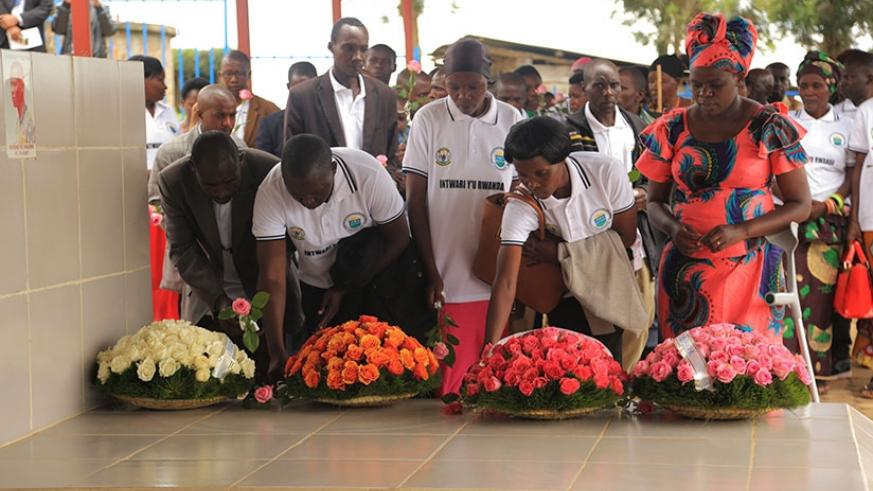 Survivors of the March 18, 1997 nighttime attack on ES Nyange school in Ngororero District lay wreaths on the grave of one of their former classmates, Valens Ndemeye, who was kille....