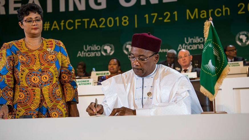 President Mahamadou Issoufou of Niger, who spearheaded the CFTA adoption process, signs the agreement in Kigali on Wednesday. Forty-four countries signed the African Continental Fr....