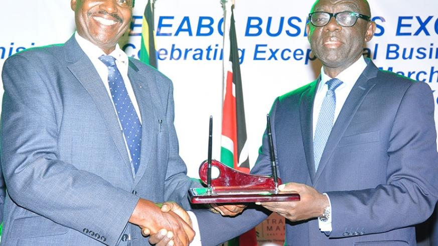 Karera (right) receives the award from Jim Kabeho, the EABC chairman. / Peterson Tumwebaze.