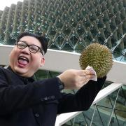 A Kim Jong Un impersonator, Howard X, poses with a durian at the Esplanade on May 27, 2018 in Singapore. / Internet photo