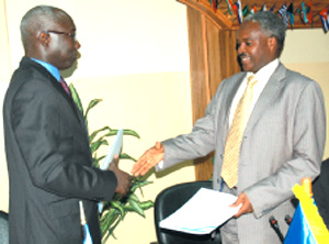 ICTR's Dieng (L) and Minister Murigande shake hands after signing the transfer agreement at the Ministry of Foreign Affairs headquarters in Kigali yesterday. (Photo/ J. Mbanda)