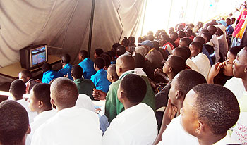 Residents of Kabutare Cell in Huye district follow proceeding of the swearing in ceremony of President Paul Kagame on television yesterday (Photo: P. Ntambara)