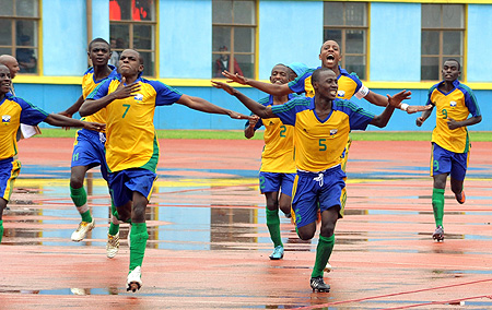 Junior Wasp's players join Charles Mwesigye (left) as he celebrates after scoring in the opening game against Burkina Faso.