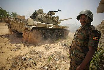 A Ugandan soldier serving with the African Union Mission in Somalia stands guard as a tank passes following an advance with the Somali National Army to capture Mogadishu University, on January 20. Net  Photo.