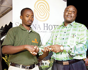 Jules Mutesa receiving his winner's trophy from the Serena Hotels Rwanda Country Manager Charles Muia on Saturday.  The New Times; T. Kisambira.
