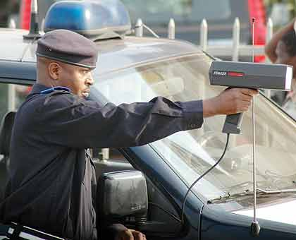 A Police officer checks traffic speed on a highway.  The New Times/File.